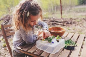 child girl exploring nature in early spring looking at first spr