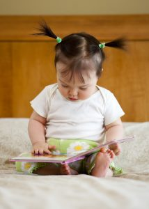 One year old baby and book