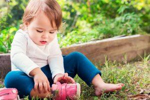 Toddler putting on shoe